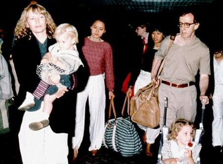 Soon-Yi Previn Farrow and her ex-partner Woody Allen with Soon-Yi (in the red), Lark (in the black top), Ronan (in Farrow's arms) and Eliza (in the pushchair) at Heathrow Airport in 1989