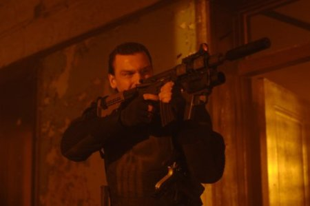 Ray Stevenson  as Frank Castle looking kick-ass with a gun in Punisher: War Zone.