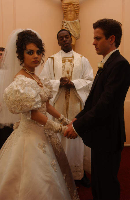 Tony 'n' Tina's Wedding Mila Kunis as Tina, Dean Edwards as Father Mark and Joey McIntyre as Tony at ceremony in Tony 'n' Tina's Wedding.