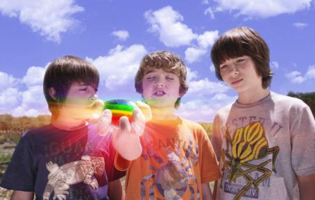 Leo Howard Kids-with-rock: Lug (REBEL RODRIGUEZ, left) and Laser (LEO HOWARD, right) watch as Loogie (TREVOR GAGNON) closes his eyes to make a wish on the rainbow rock in Warner Bros. Pictures' family action adventure comedy 'Shorts.' Photo courtesy of W
