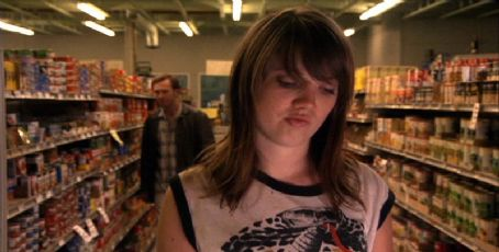 Barb (Nicki Clyne) shopping while Earl (Peter Outerbridge) approaches.