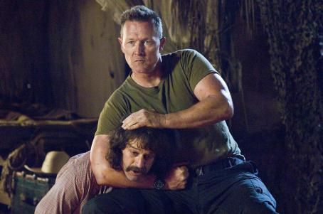 "Robert Patrick TV soundman Fred Wolf (Allen Covert, left) gets caught in a headlock from macho Gus Hayden (, right) in his quest to find Bigfoot in ""Strange Wilderness."" Photo Credit: Darren Michaels. © 2007 by Paramount Pictures. All Rights Re"