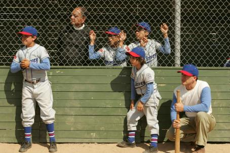 Moises Arias Enrique (Jansen Panettiere), Padre Esteban (Cheech Marin, behind fence), Mario () and Cesar (Clifton Collins, Jr., kneeling) in THE PERFECT GAME. Photo credit: Vivian Zink