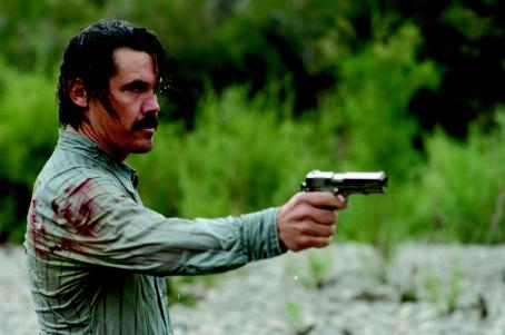 No Country for Old Men Moss (JOSH BROLIN) gets out of the river onto a sandbar and shoots at the dog chasing him