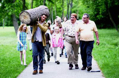 Tony Goldwyn  carrying an enormous log while astonished townspeople follow in Crusader's Joshua - 2002