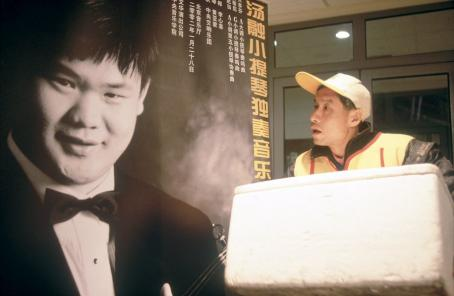 Peiqi Liu - Liu Cheng (Liu Peiqi) examines an advertisement for a concert by Tang Rong (Li Chuan Yun), another violin prodigy