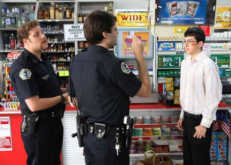 Bill Hader Fogell (Christopher Mintz-Plasse, right) – posing as McLovin, the 25-year-old Hawaiian organ donor – gets asked for some identification by two clueless cops, Officer Michaels (Seth Rogen, left) and Officer Slater (, center), in Super