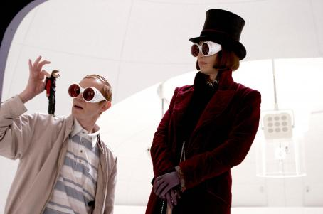 "Adam Godley - ADAM GODLEY as Mr. Teavee holds up a miniaturized JORDAN FRY as Mike Teavee and JOHNNY DEPP as Willy Wonka looks on in Warner Bros. Pictures' fantasy adventure ""Charlie and the Chocolate Factory."" Photo by Peter Mountain"