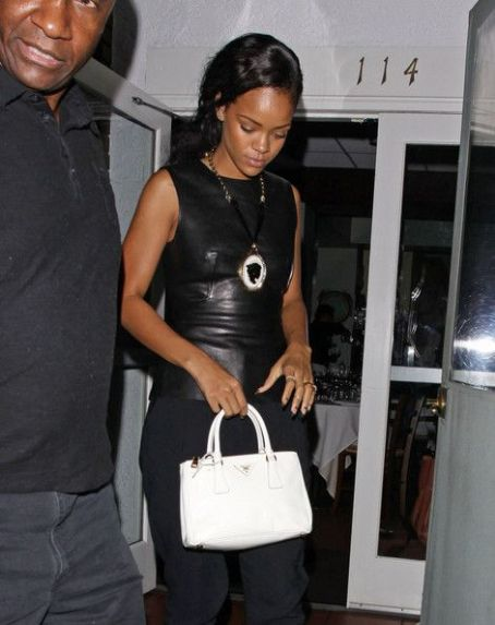 Rihanna shields her eyes from camera flashes as she leaves Il Ristorante di Giorgio Baldi