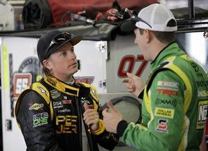Kyle Busch Kimi Raikkonen, left, of Finland, talks with , right, during practice for the NASCAR truck series North Carolina Lottery 200 auto race in Concord, N.C., Friday, May 20, 2011. (AP Photo/Terry Renna)