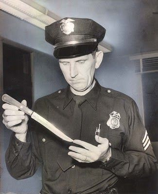 Johnny Stompanato Police Officer holding knife used by Lana Turner's daughter, Cheryl, to kill